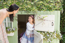 Mother And Daughter At Playhouse In Garden