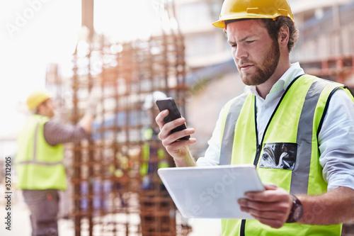 Construction worker digital tablet texting cell phone at construction site Tapéta, Fotótapéta