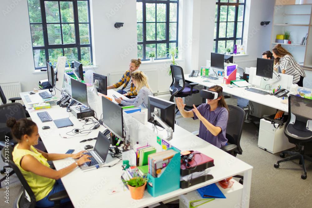 Fototapeta Designers and computer programmers working in open plan office