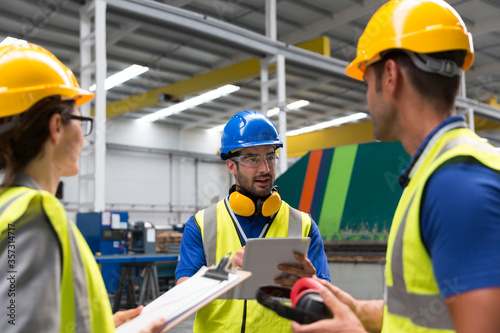 Supervisor and workers with clipboard and digital tablet talking in factory Wallpaper Mural