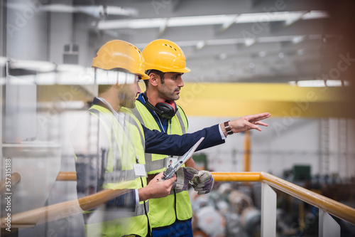 Male supervisors with clipboard talking on platform in factory Canvas Print