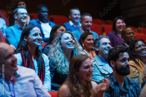 Smiling, enthusiastic audience in dark auditorium Fototapeta