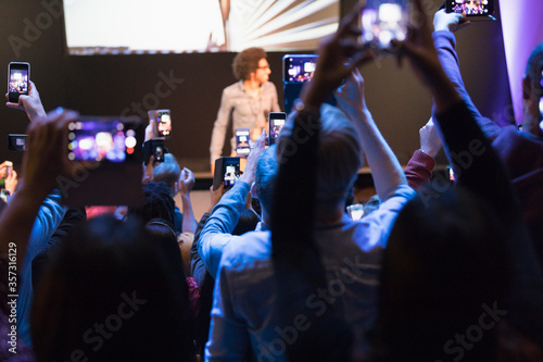 Obraz Audience with camera phones photographing speaker on stage - fototapety do salonu