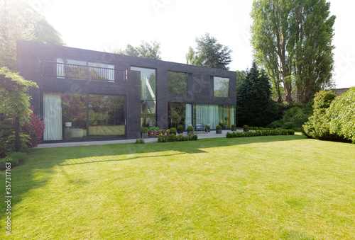 Leinwand Poster Modern house and sunny, landscaped yard