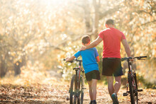 Affectionate Father And Son Walking Mountain Bikes On Path In Woods