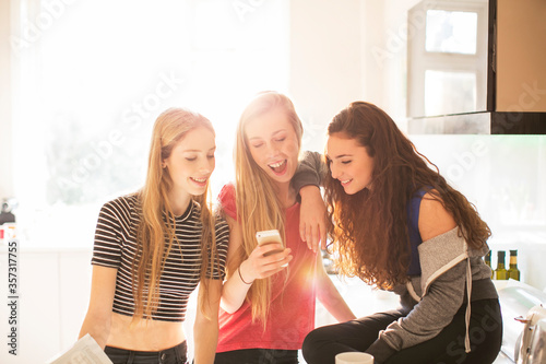 Photo Teenage girls texting with cell phone in sunny kitchen