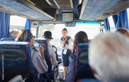 Fotografía Female tour guide with microphone talking to active senior tourists on tour bus