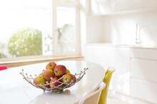 Apples In Wire Basket On Modern Kitchen Table