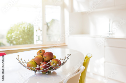 Photo Apples in wire basket on modern kitchen table