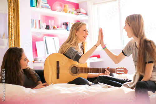 Teenage girls with guitar high fiving on bed Wallpaper Mural