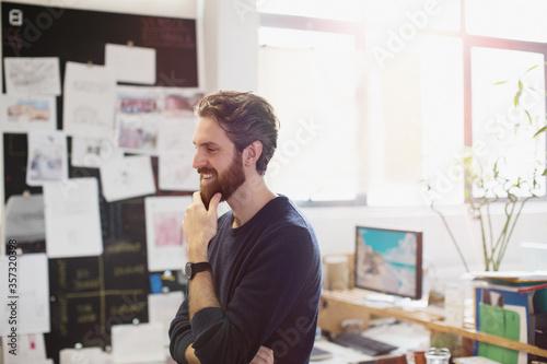 Fotografiet Happy creative businessman rubbing beard in office