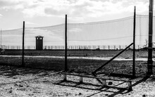 Grayscale Shot Of A Concentration Camp Behind The Fence