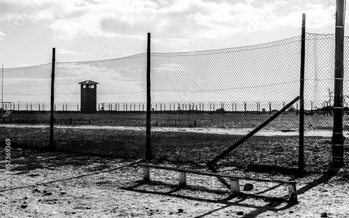 Photo Grayscale shot of a concentration camp behind the fence