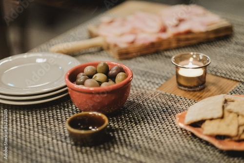 Close up shot of a meal including olives in nice ceramic dishes next to a  lit candle