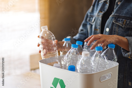 Photo A woman collecting and separating recyclable garbage plastic bottles into a tras