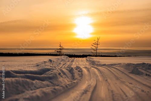 Fototapeta Scenic winter landscape of sundown over snowy road across the frozen river Yenisei in Siberia. obraz