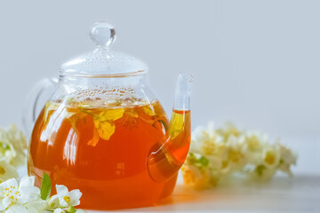 glass teapot with hot tea and Jasmine flowers. background with a teapot with tea and branches of blooming Jasmine.