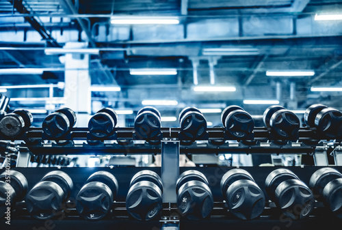 Fototapeta rows with a set of dumbbells in the gym obraz