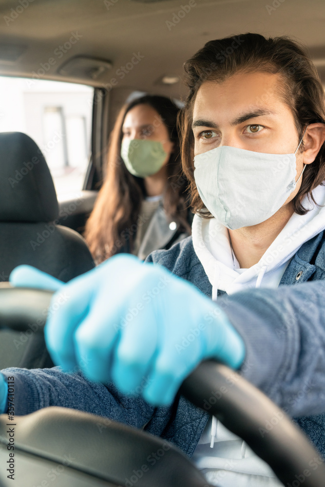 Fototapeta Serious young man in cloth mask and gloves driving taxi client during coronavirus