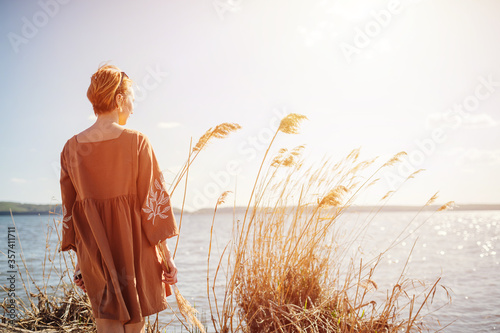 Woman with short hair standing on a lake shore, looking afar Wallpaper Mural