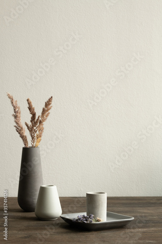 Fotografie, Tablou Two white ceramic vases standing on wooden table on background of black one