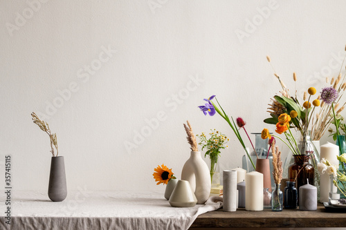 Photo Black handmade ceramic or clay jug with dried wildflowers standing on table