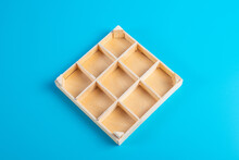 A Small, Wooden Box With Storage Trays. Empty Box On A Blue Background.