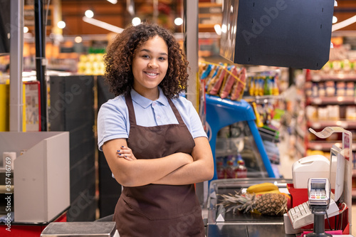 Girl in apron standing by cashbox in supermarket and crossing arms by chest