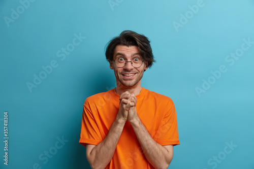 Cheerful man anticipates for something wonderful happen, keeps hands pressed together, smiles and cannot wait, has eyes full of happiness, wears casual outfit, isolated over blue background Canvas Print