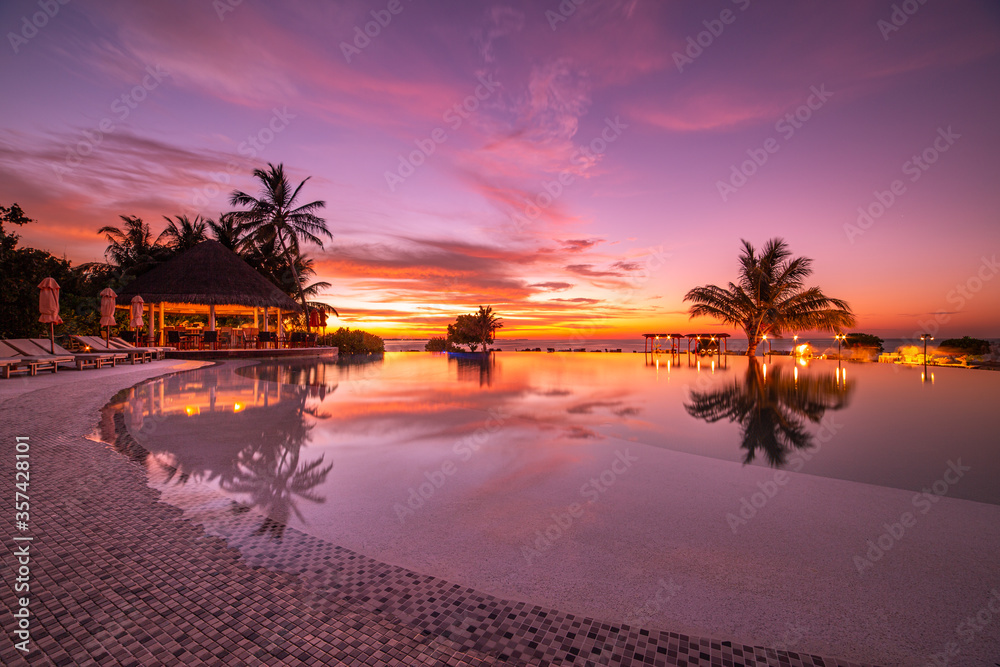 Fototapeta Beautiful poolside and sunset sky. Luxurious tropical beach landscape, deck chairs and loungers and water reflection. Outdoor tourism landscape. Luxurious beach resort. Summer travel and vacation