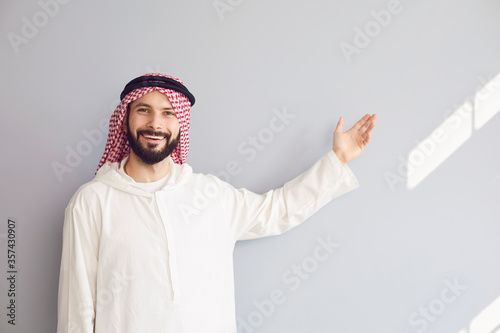 Fotografija Attractive smiling arab man points his hand to a gray background