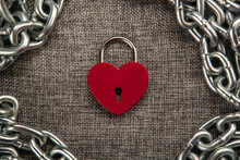 Red Locked Heart Shaped Padlock With Steel Chain On Gray Linen Textile