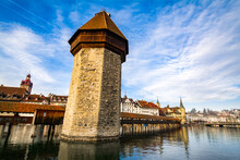 The Tower Of The Kapellbrucke (Literally Chapel Bridge) Across Reuss River With Lake Lucerne In The Background In Lucerne, Switzerland
