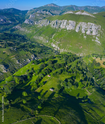 Fototapeta Spring landscape of mountains, meadows of mowing and cabins pasiegas in the Valle del Miera, Cantabria, Spain, Europe obraz na płótnie