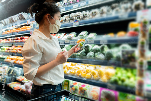 Obraz new normal after covid epidemic young smart asian female shopping new lifestyle in supermarket with face shild or mask protection hand choose fresh vegetable of fruit new normal lifestyle - fototapety do salonu