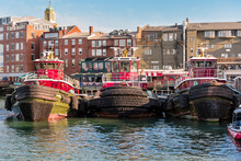 Row Of Tug Boats Tied Up To A Dock With Traditional Residential Buildings And Restaurants In Background On A Sunny Autumn Day. Portsmouth, NH, USA.
