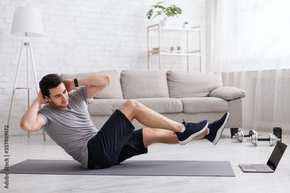 Fototapeta Sport and healthy lifestyle. Man does exercises for abdominal muscles and watches online training