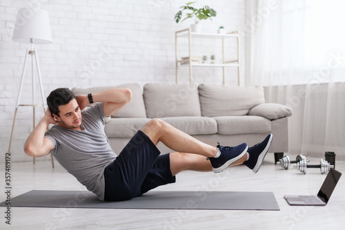 Fototapeta Sport and healthy lifestyle. Man does exercises for abdominal muscles and watches online training obraz