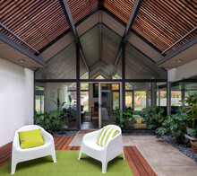 Modern Living Room That Is Bright And Airy With Lots Of House Plants, Slanted Roof