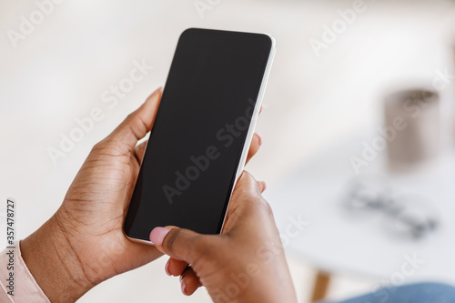Fotografie, Obraz Mockup of smartphone with black screen in hands of unrecognizable black woman