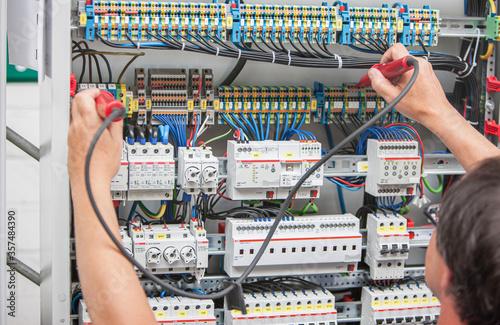Photo Ein Elektriker misst die Spannung in einer elektrischen Anlage
