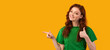 Millennial Girl Pointing Finger Aside Gesturing Thumbs Up, Yellow Background