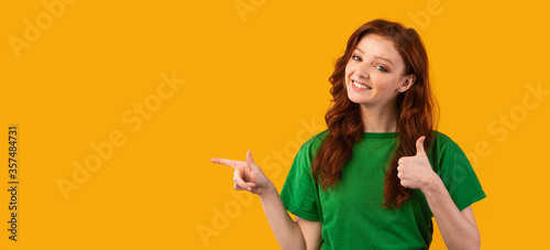 Millennial Girl Pointing Finger Aside Gesturing Thumbs Up, Yellow Background Canvas Print