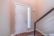 White Hinged Wooden Front Door And Sidelight Viewed From Inside Of Home