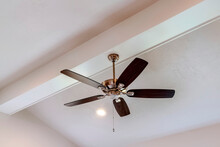 Decorative Wood Beam With Standard Ceiling Fan And Lights Inside A House