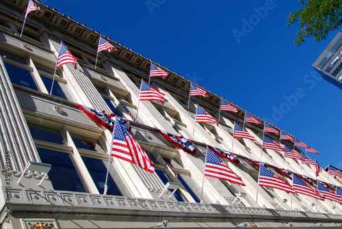 Fototapeta many American flags at facade of building