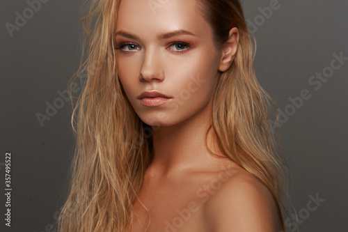 Closeup face fashion beauty portrait of young beautiful caucasian blonde woman with wet hair and makeup posing against gray background Canvas Print