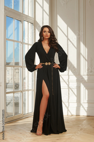 Young woman with brown wavy hair in long black elegant evening dress standing in luxury white interior with french window on a sunny day Fototapet