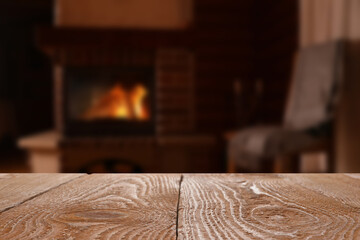 Rustic table and fireplace with burning wood indoors