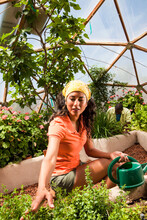 Hispanic Couple Gardening In Geodesic Dome Greenhouse